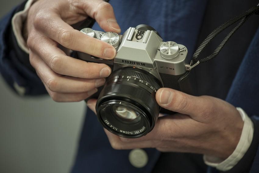 Беззеркальная камера в руках.