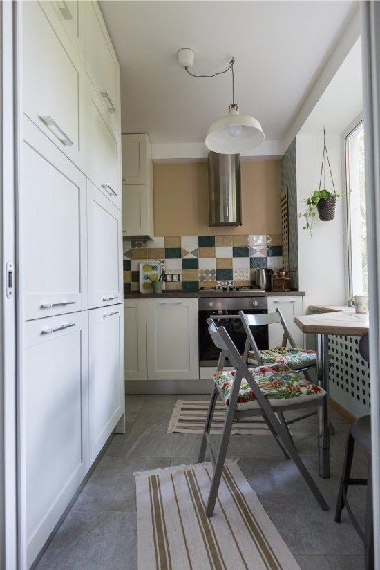 Встраиваемый холодильник в маленькой комнате.