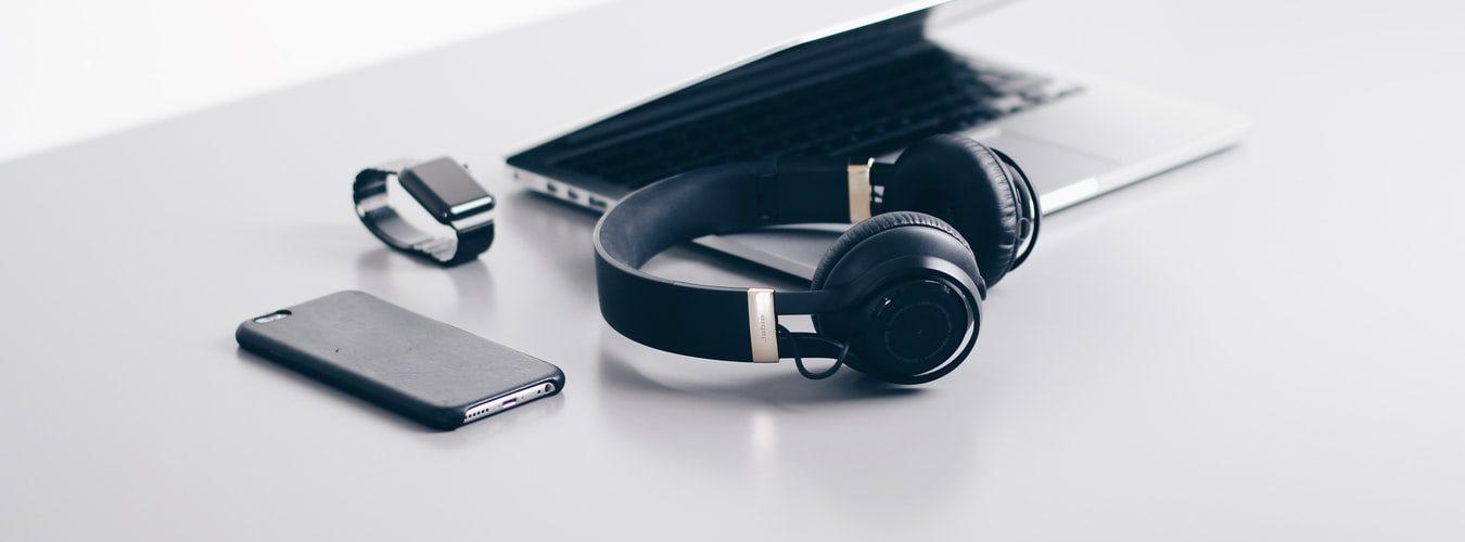 Ноутбук, смартфон, наушники и часы лежат на столе